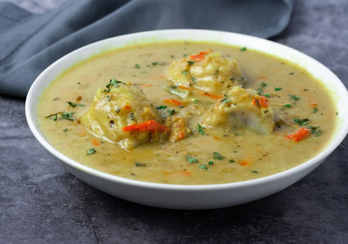 Vegan chicken and dumplings in a white bowl on a grey background