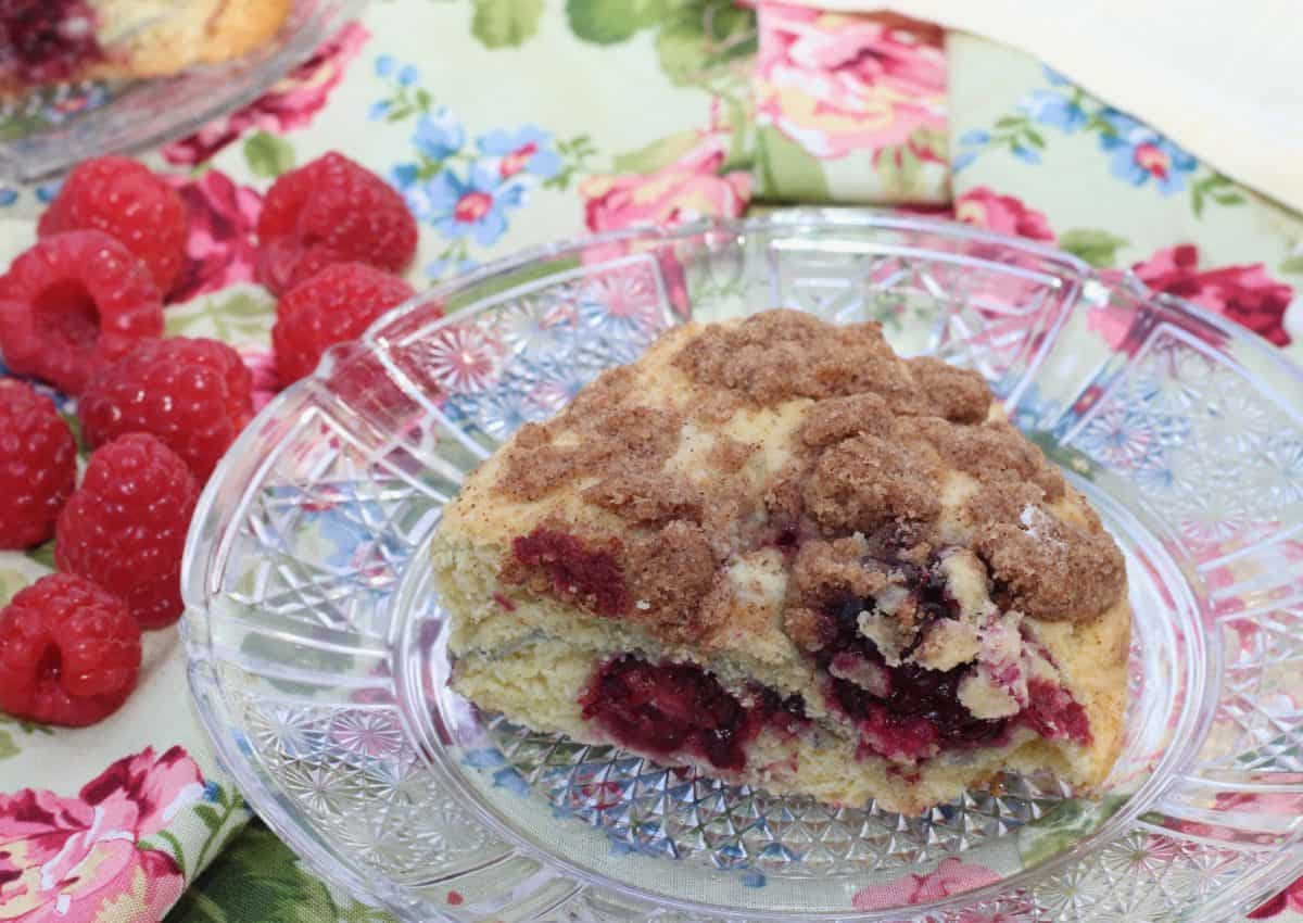 one scone filled with berries on a clear plate next to a handful of raspberries.