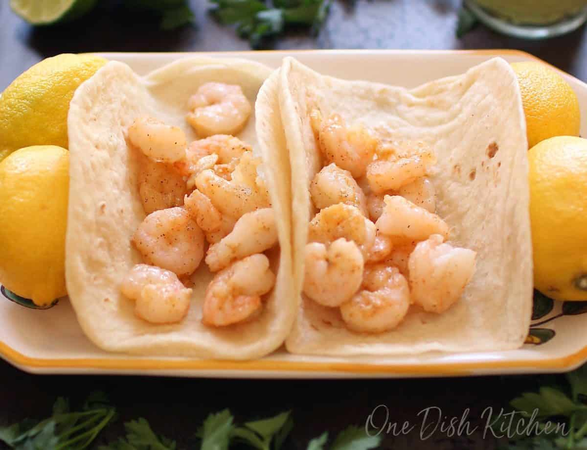 Two flour tortillas filled with shrimp on a plate surrounded by four whole lemons