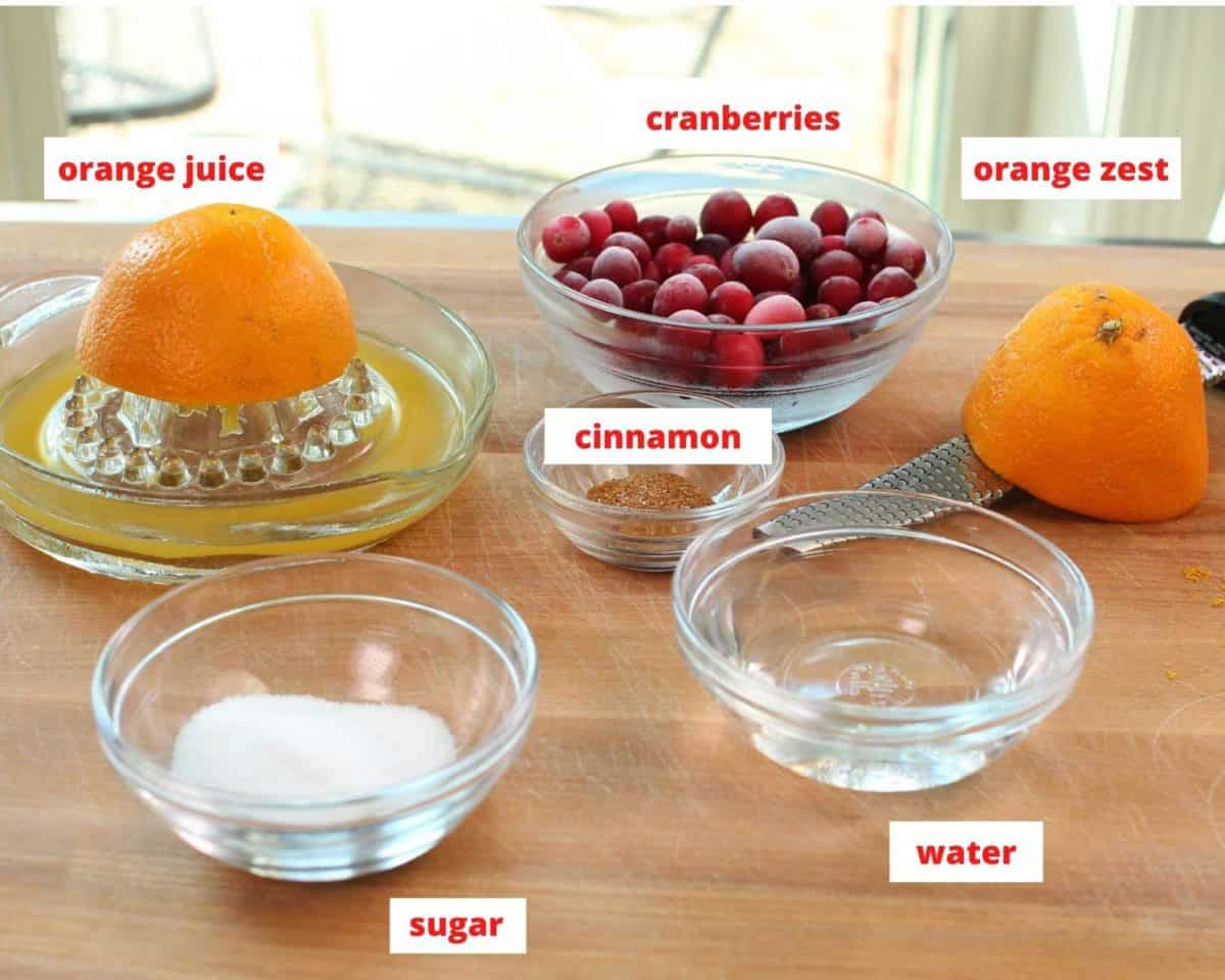 ingredients needed for making cranberry jam on a brown table.