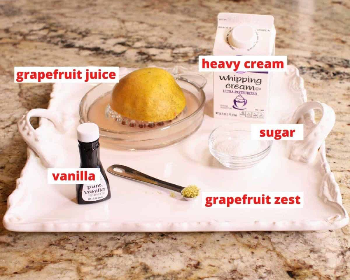 cream, half of a grapefruit, vanilla, and sugar on a white tray sitting on a brown granite kitchen counter.