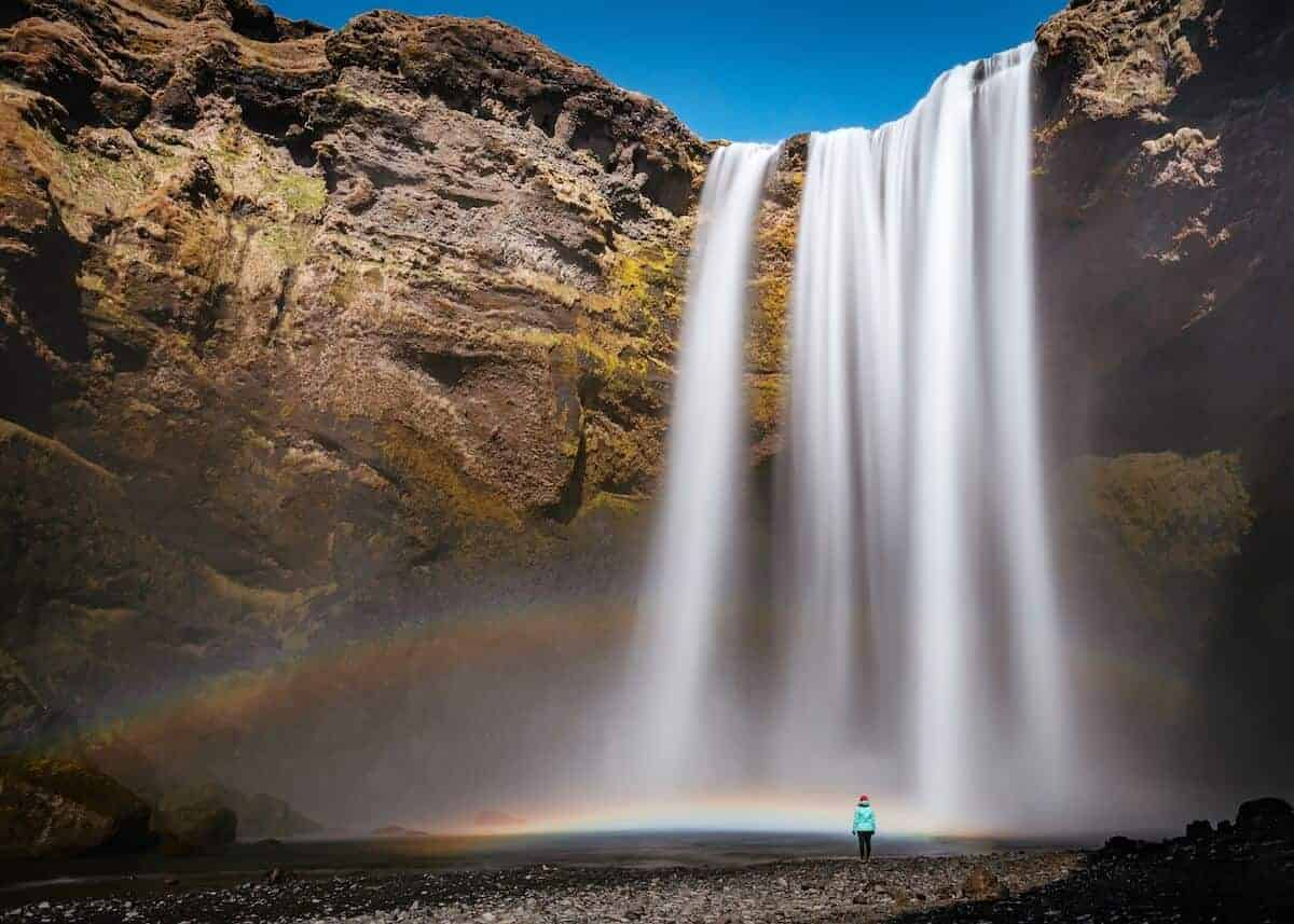 Cover Image for What to Pack for Iceland featuring a woman stood in a blue jacket and red hat in front of a waterfall in Iceland
