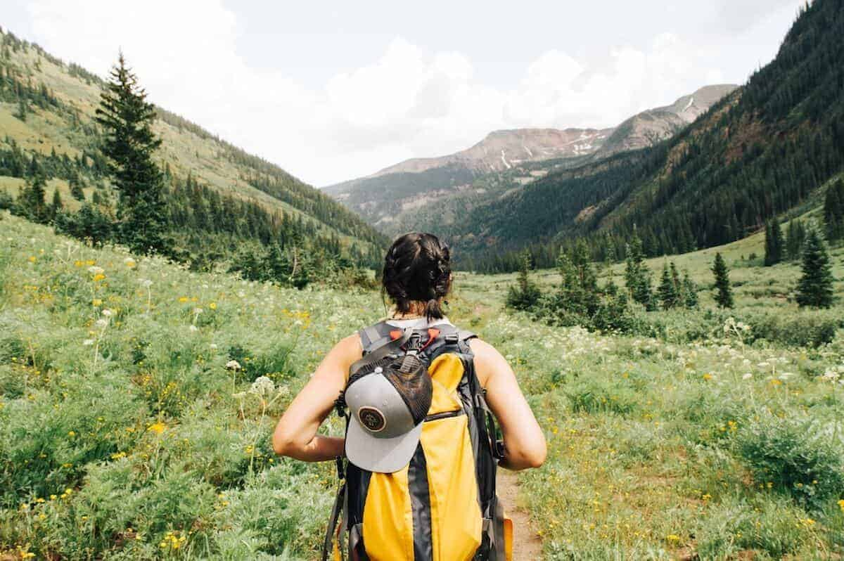 Eco Friendly Gifts for Travel - female traveler looking out across a green field wearing a backpack