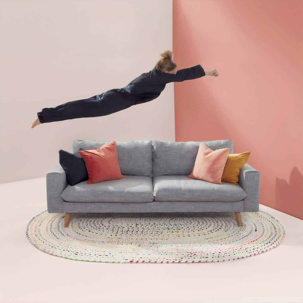 How to Travel at Home - woman 'fyinf' above a grey 2 seater couch
