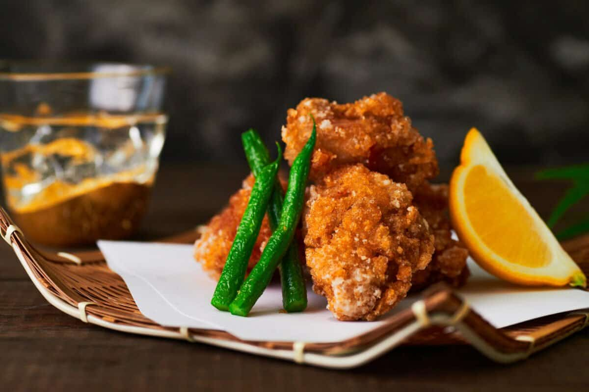 Crisp Chicken Karaage with green beans and a wedge of lemon.