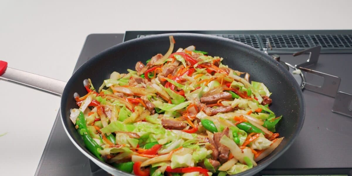 Chop Suey with pork, cabbage, carrots, peppers, snap peas, celery and onions in a frying pan.