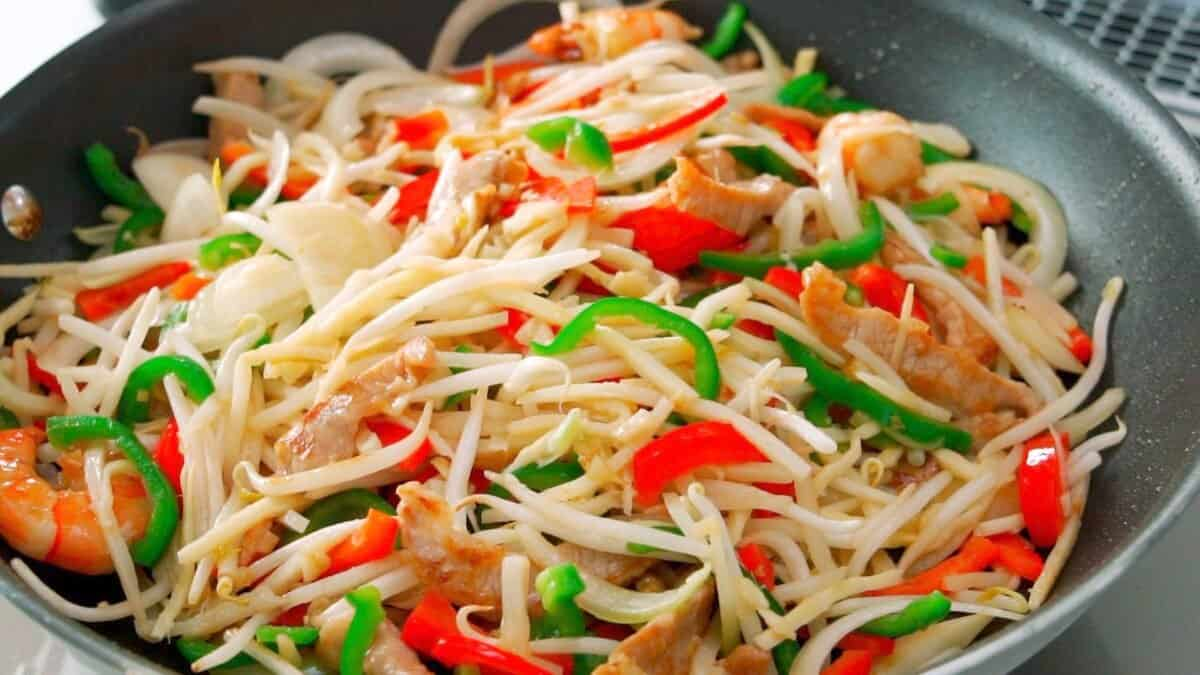 Onions, bell peppers, beansprouts and bamboo shoots being stir-fried for Singapore Rice Noodles.