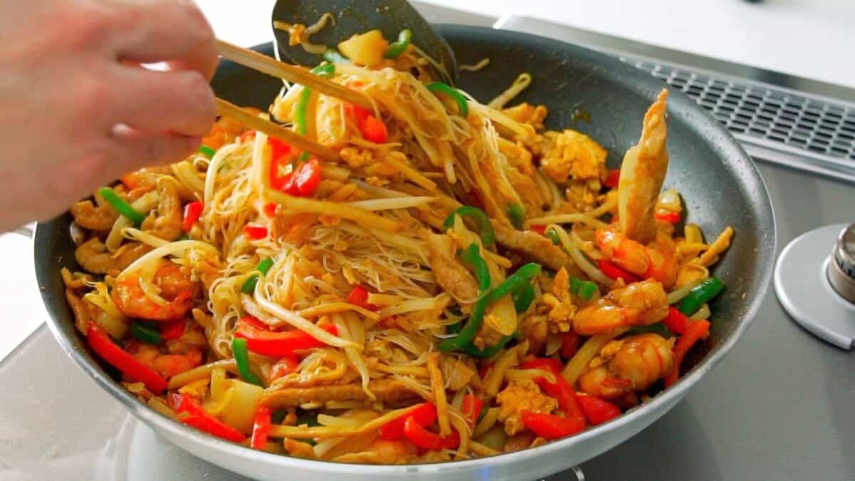 Tossing Singapore Noodles in a frying pan with chopsticks and a spatula.