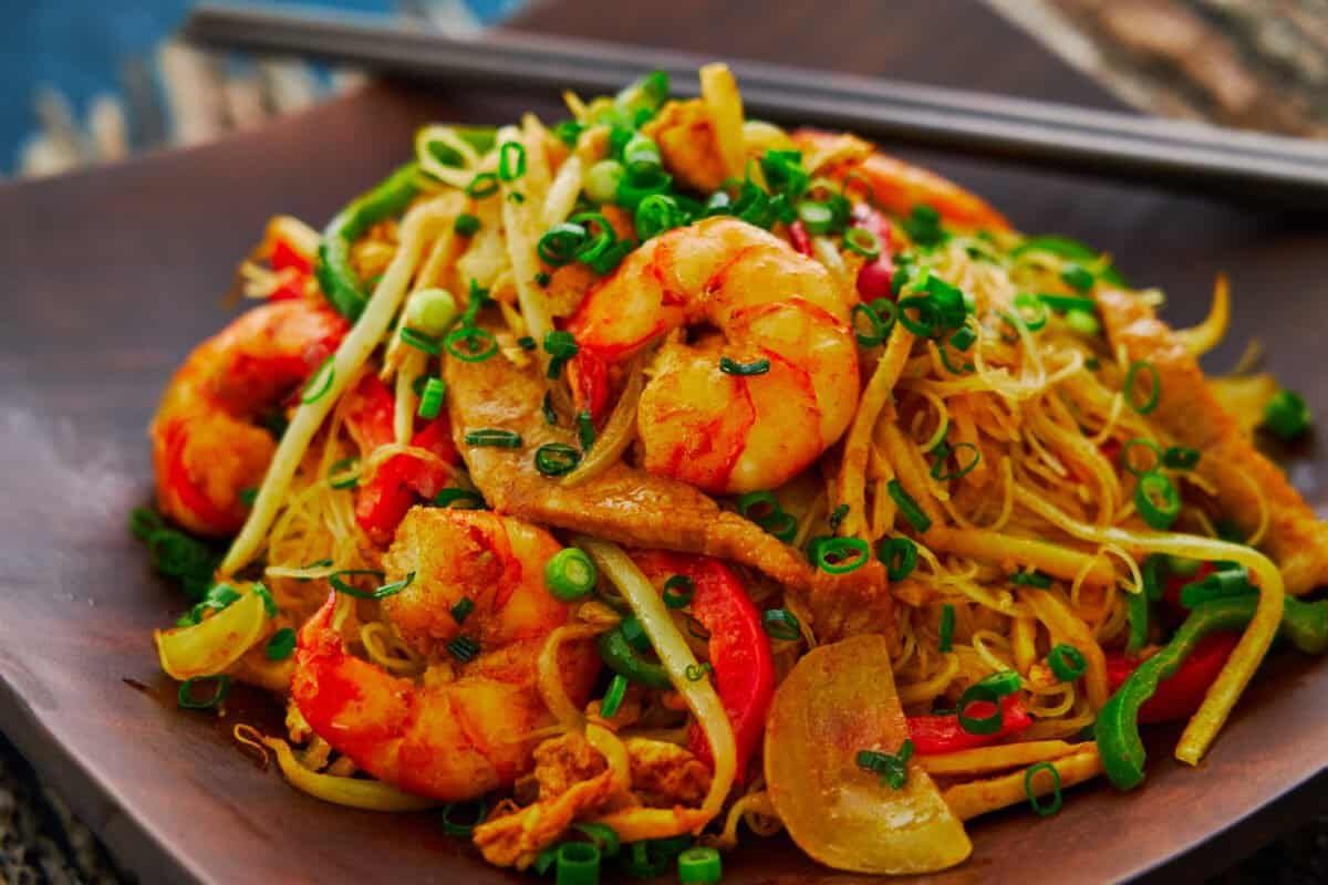 A mouthwatering plate of curry-flavored Singapore Noodles loaded with shrimp, pork, bean sprouts, and bell peppers.