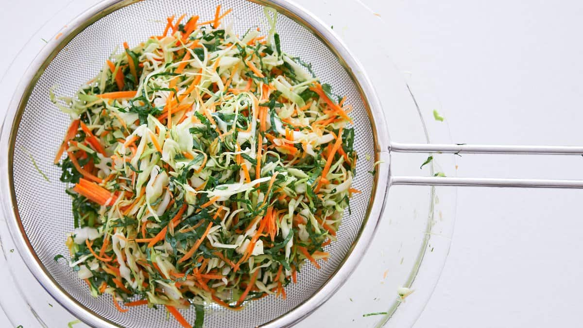 Cabbage, carrot and kale coleslaw salted and draining in a strainer.