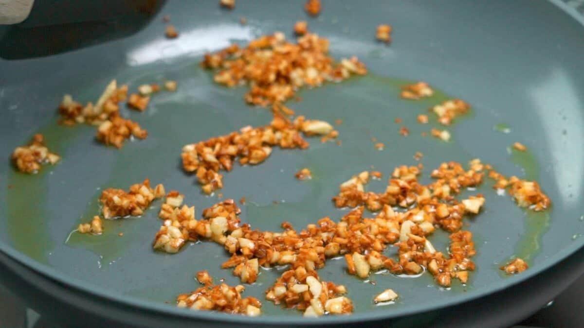 Frying garlic in oil until browned and crisp.