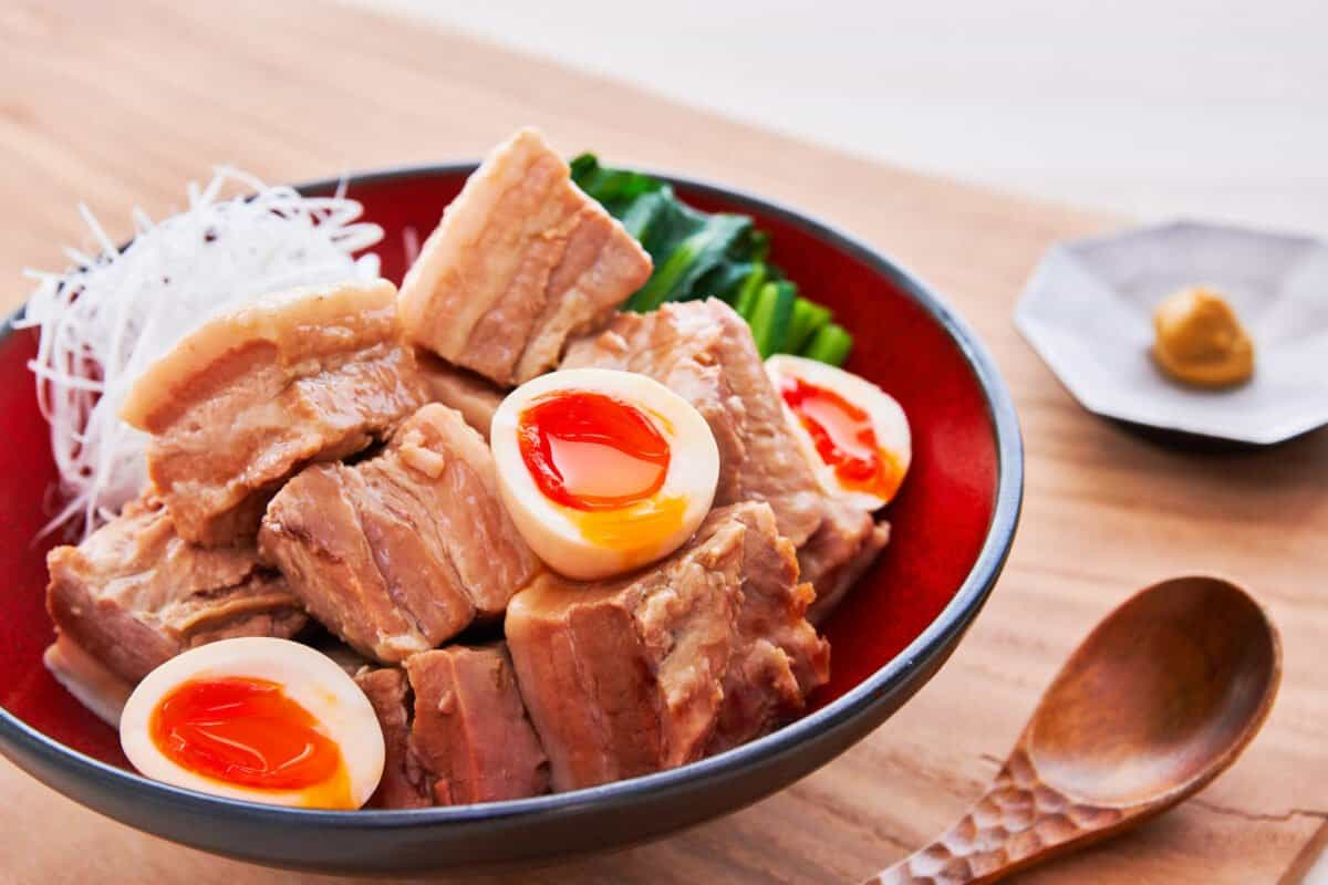 Kakuni is a Japanese dish that's made with cubes of pork belly that are braised with aromatics until fall-apart tender. As a bonus, you can make ramen eggs by soaking soft-boiled eggs in the braising liquid.