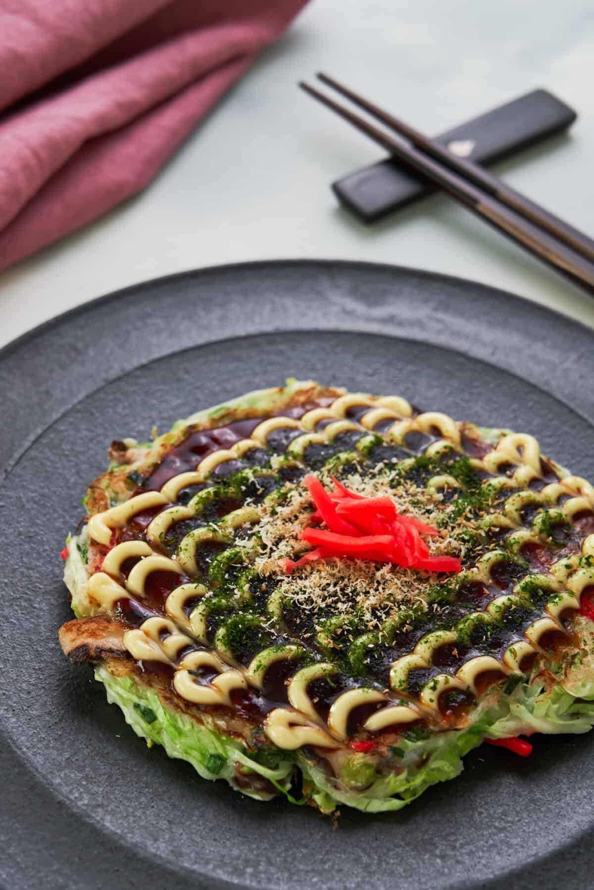 Okonomiyaki is a vegan-friendly Japanese cabbage pancake that can be loaded up and topped with all of your favorite ingredients!