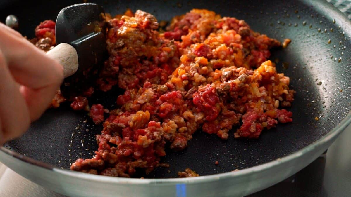 Ground beef and pork that have been added to the caramelized aromatics for making spaghetti sauce.