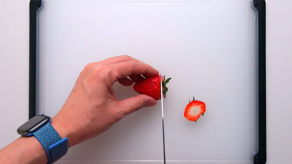 Removing the tops from strawberries.