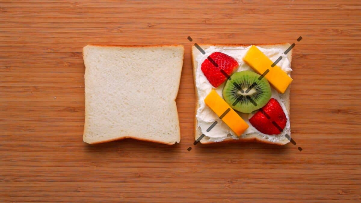 Lining up the fruit symmetrically along the cut lines for the fruit sandwich helps ensure you get an even cross section of fruit.