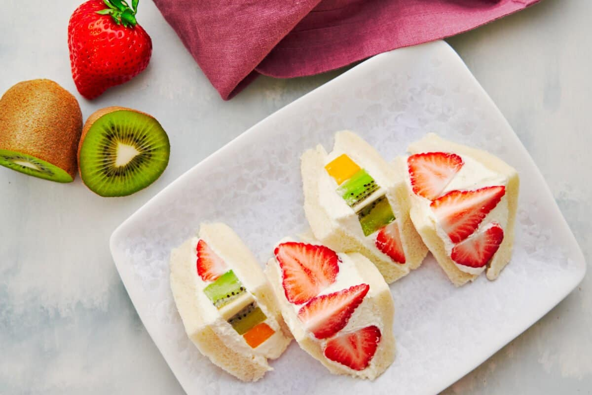 Japanese-style fruit sandwiches loaded with fresh fruit and whipped cream.