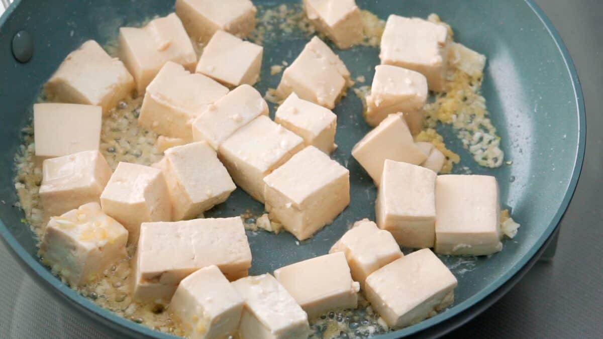 Browning marinated tofu in a frying pan.
