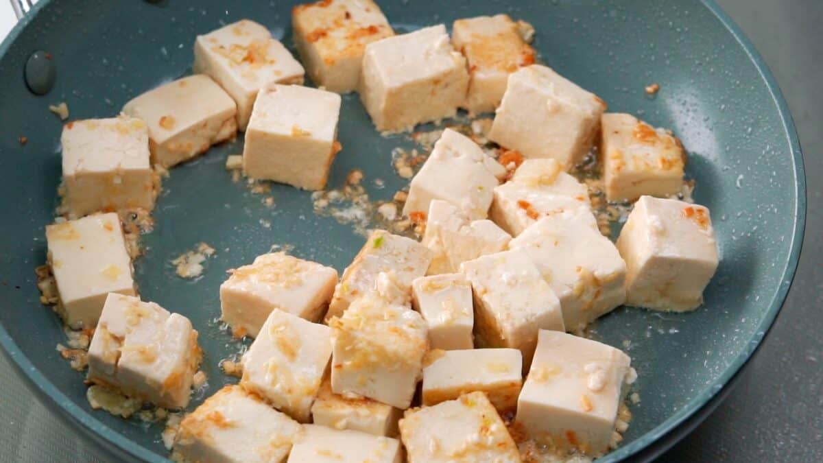 Tofu, ginger and garlic browned in a frying pan.