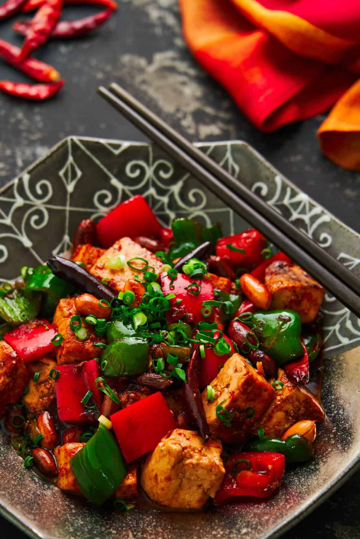 With meaty chunks of tofu that are seasoned to the core, crunchy peanuts, and crisp peppers glazed in a mouthwatering savory, sweet, sour, and spicy sauce, this easy Kung Pao Tofu is a delicious stir-fry that may be meatless, but it's flavor full!