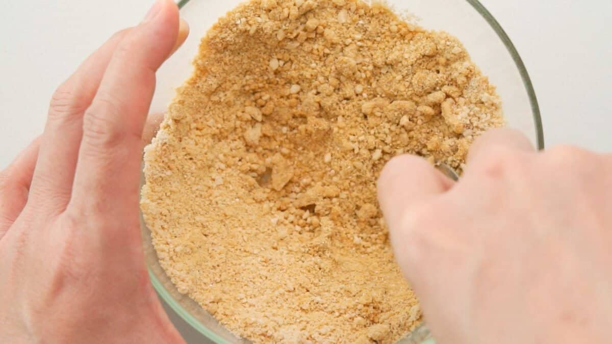 Mixing vegan parmesan cheese in a glass bowl.
