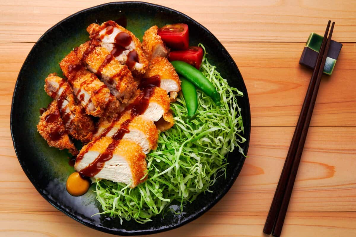 Crispy Chicken Katsu drizzled with katsu sauce on a green plate with shredded cabbage, tomatoes, and snap peas.