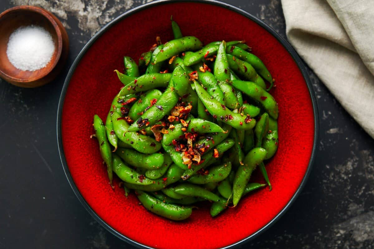 Edamame with garlic, black pepper, and chili peppers in a red bowl on a dark surface.
