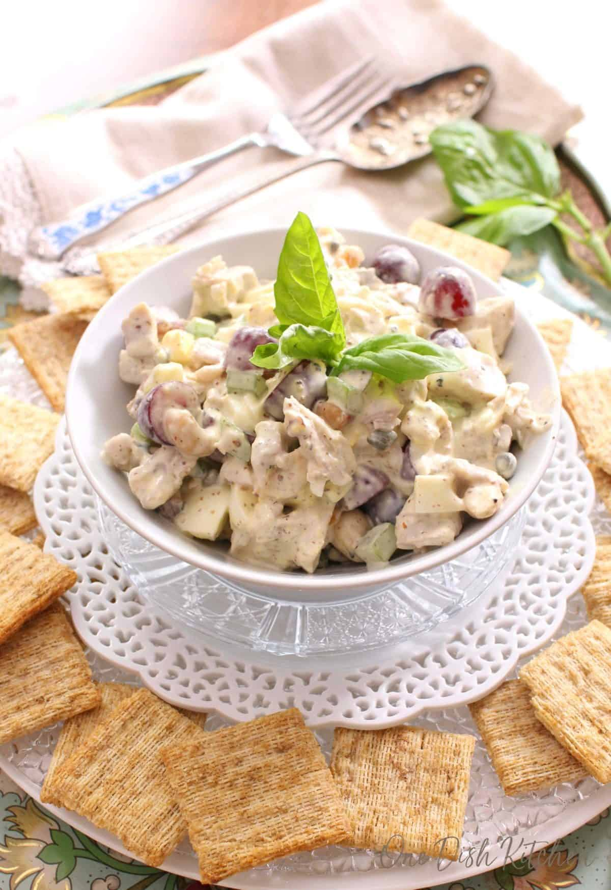 white bowl filled with chicken salad surrounded by wheat crackers.