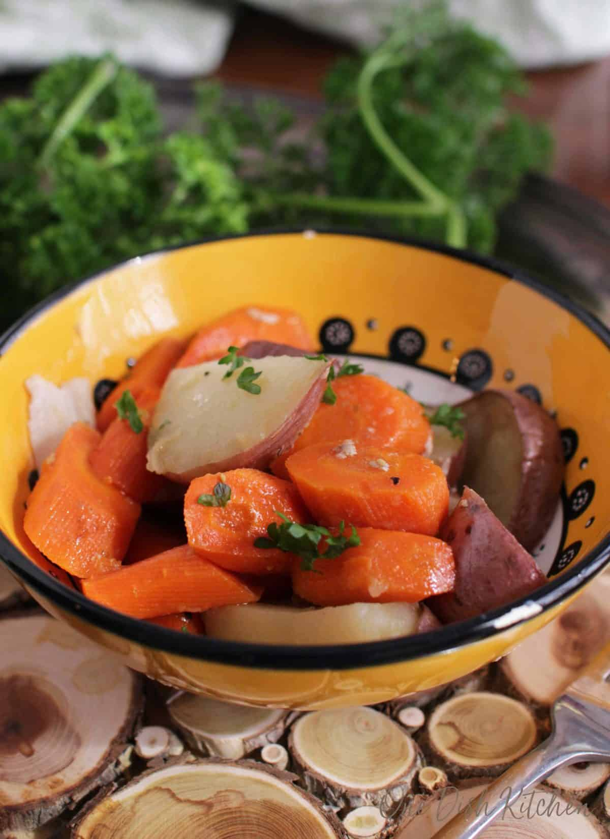 Roasted sliced red potatoes and carrots in a small bowl on a wooden trivet with a fork