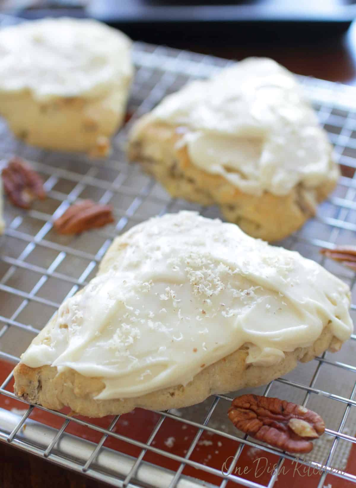 three frosted scones on a cooling rack