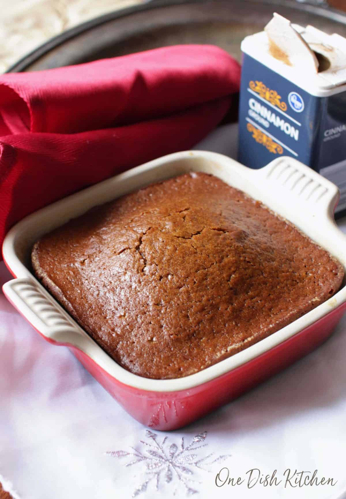 a small gingerbread cake in a red baking dish.