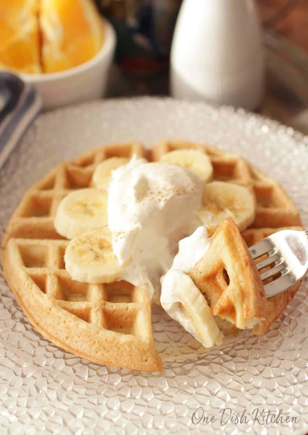 A forkful of waffle with whipped cream, banana slices, and dusted with cinnamon on a large plate