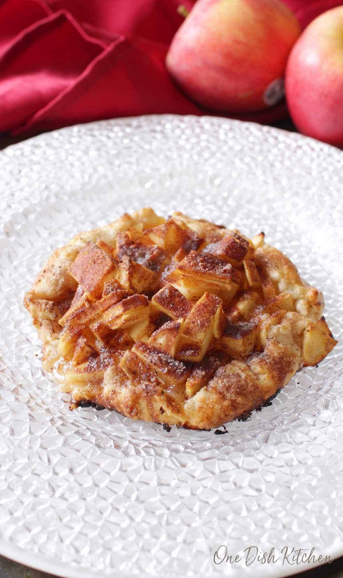 An apple galette topped with cinnamon and sugar plated with apples and a red cloth napkin in the background