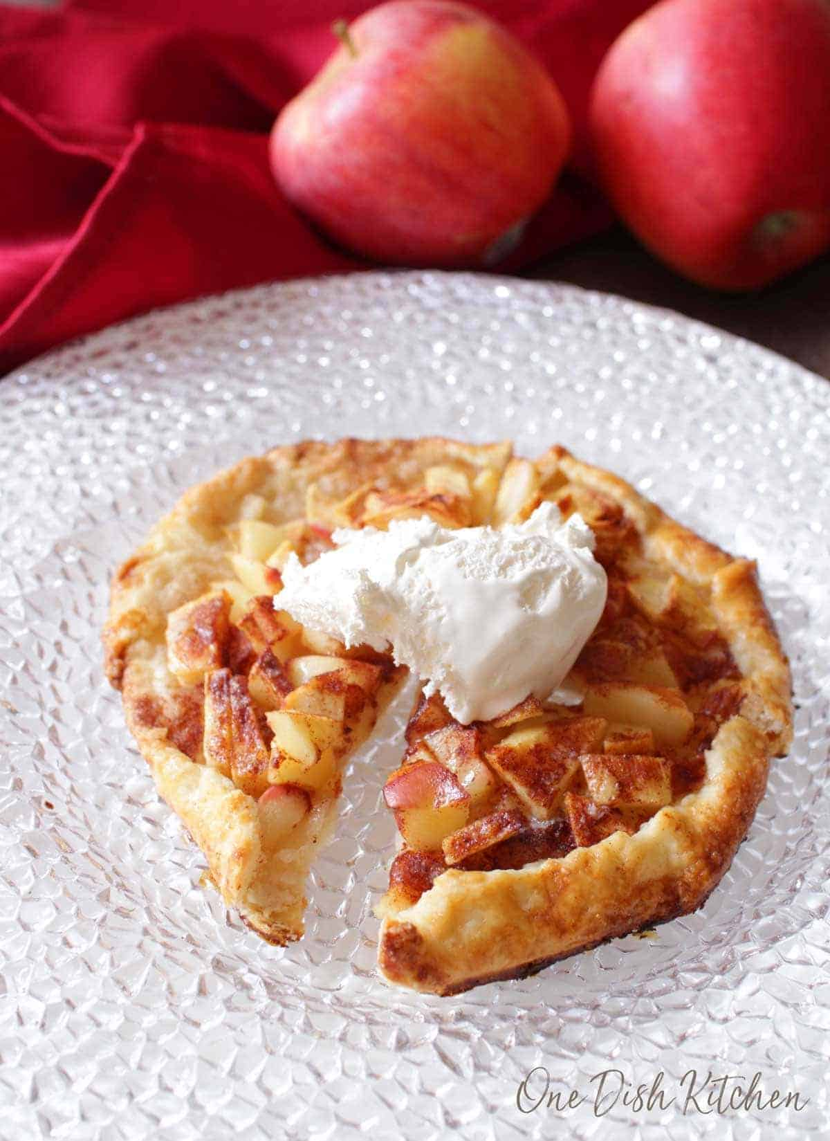 An apple galette topped with whipped cream cut into four slices
