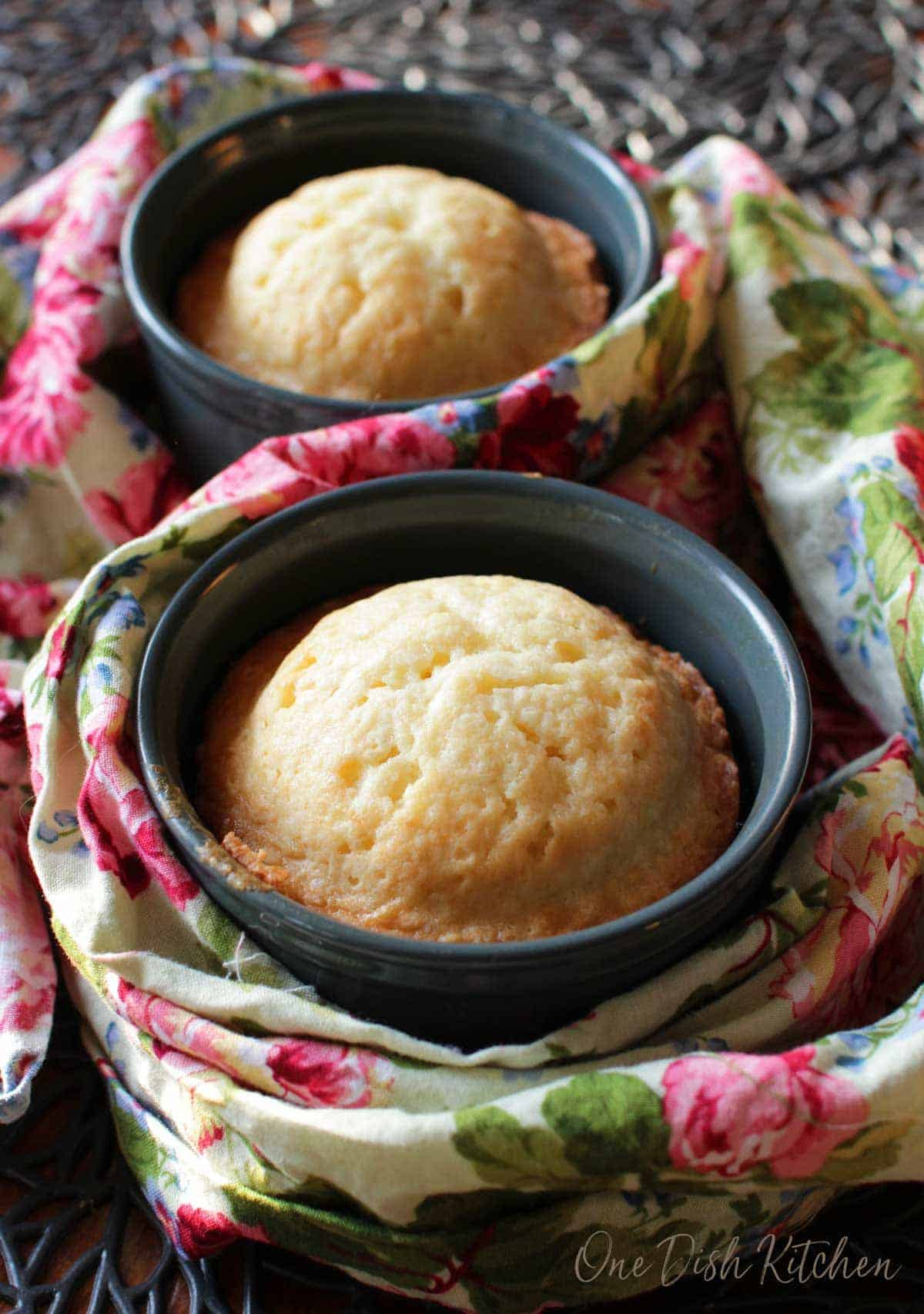 Two green ramekins filled with pound cake on a floral napkin.