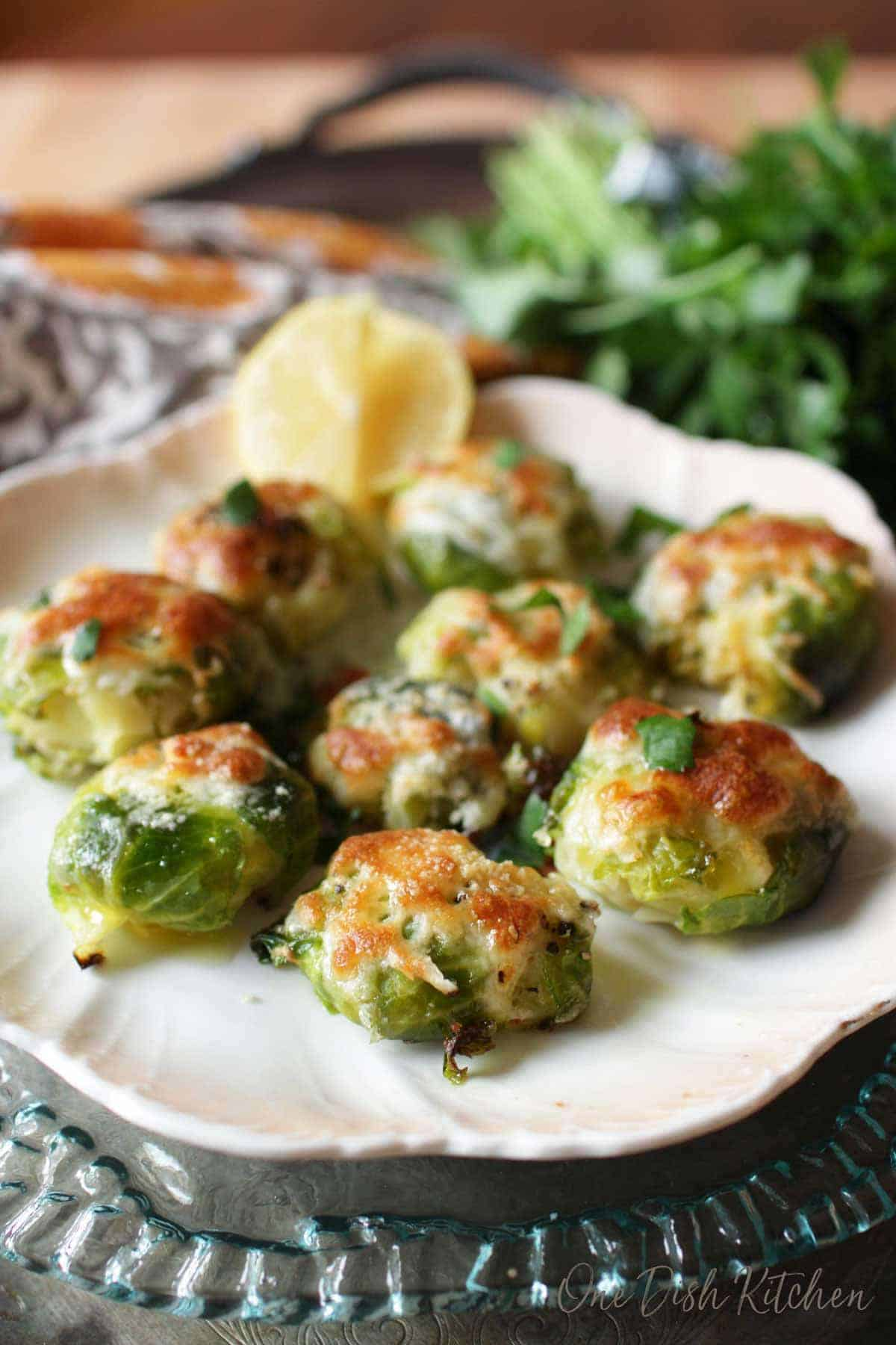 A plate of cheesy smashed brussels sprouts garnished with lemon slices