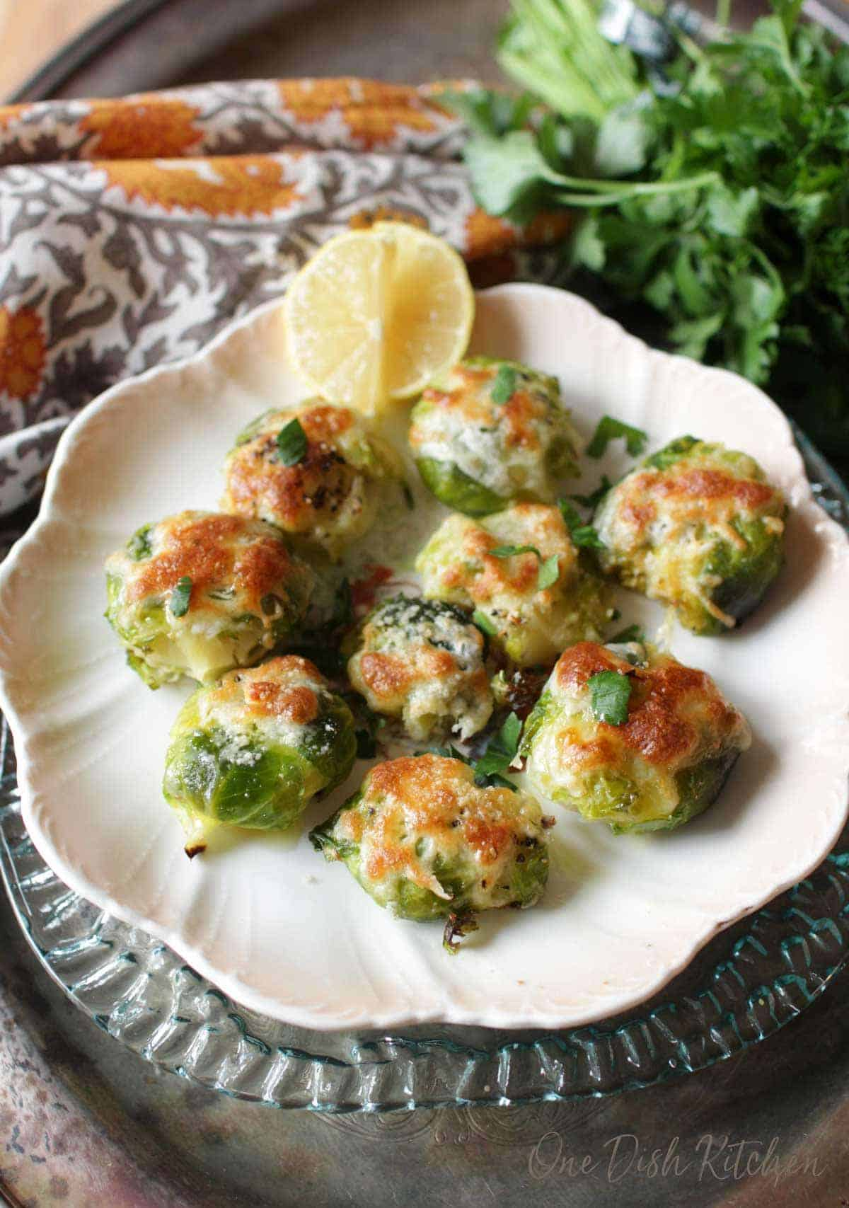 An overhead view of a plate of cheesy smashed brussels sprouts garnished with lemon slices