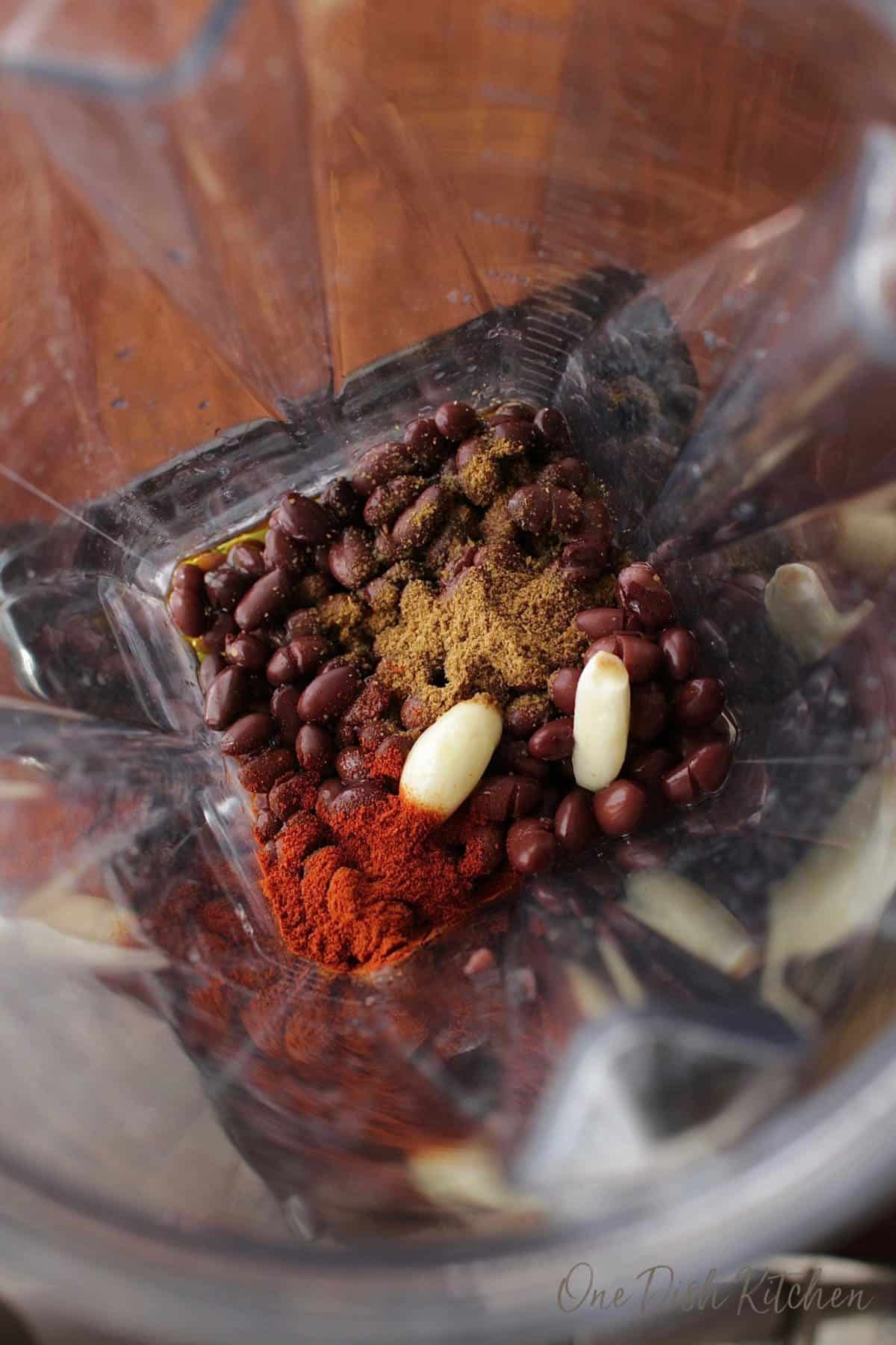 Black beans, garlic cloves, and spices in a blender