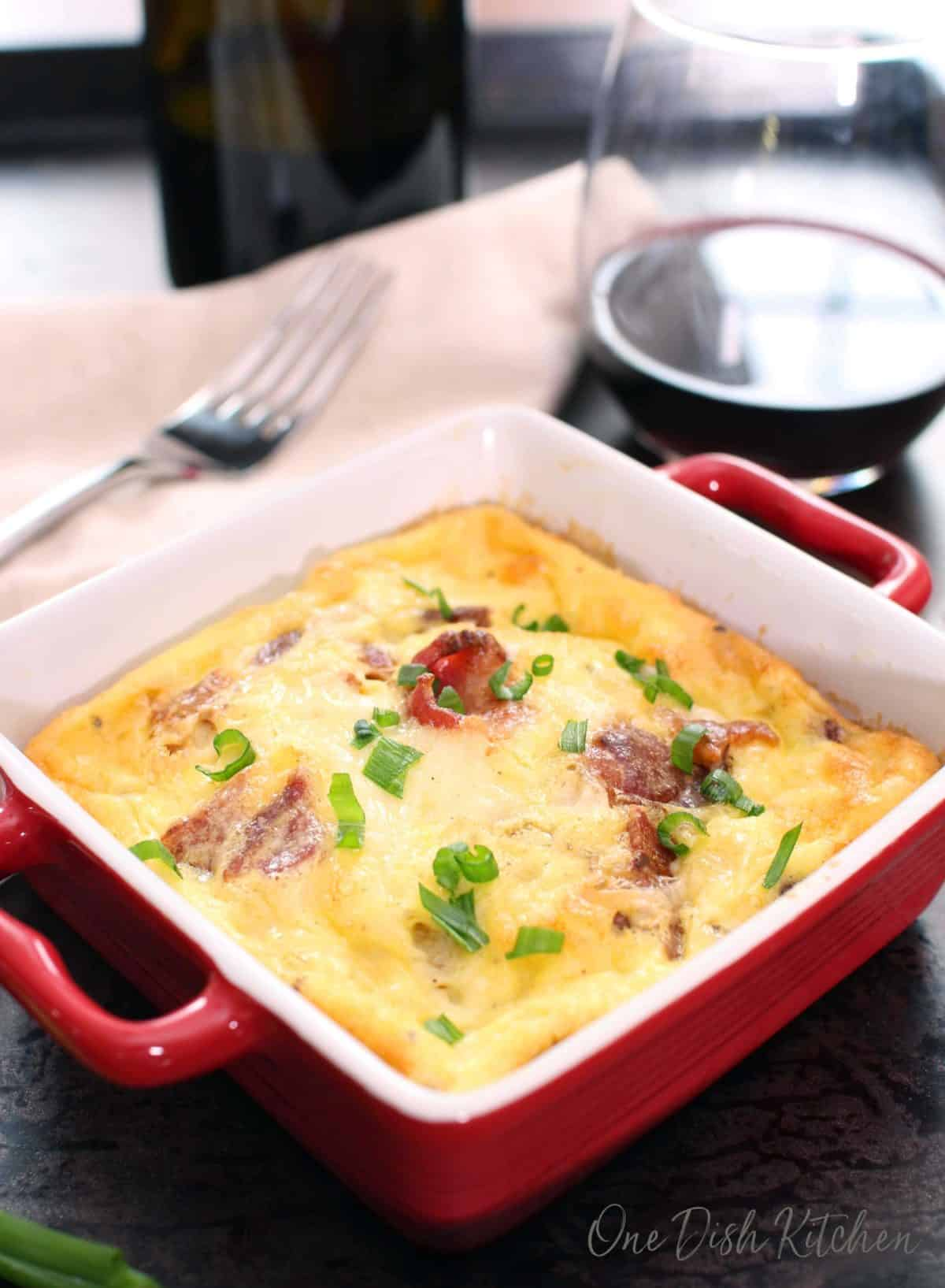 Crustless quiche lorraine baked in a small baking dish on a tray with a glass of red wine