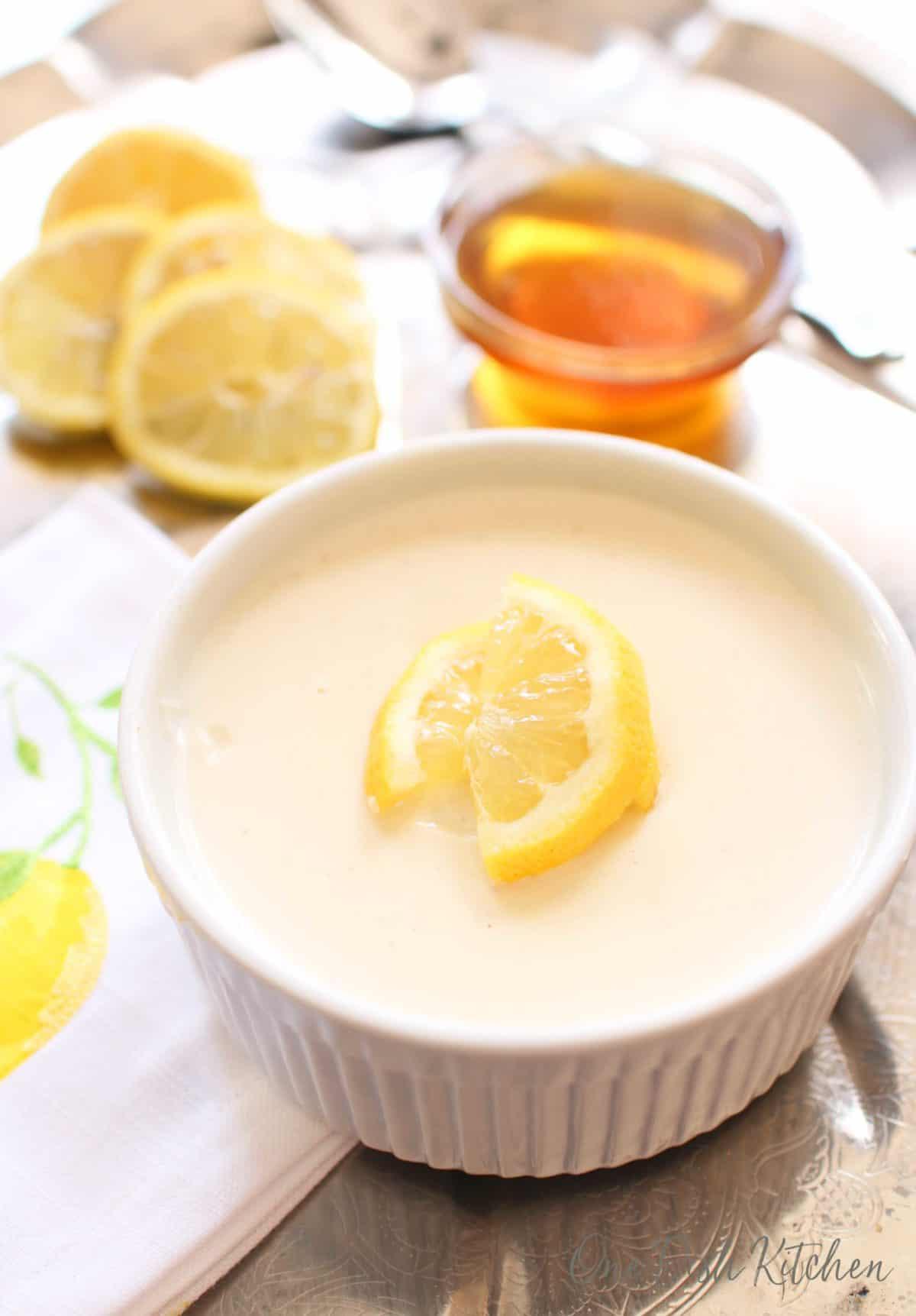 Honey lemon custard in a small ramekin next to sliced lemons and a small bowl of honey all on a metal tray