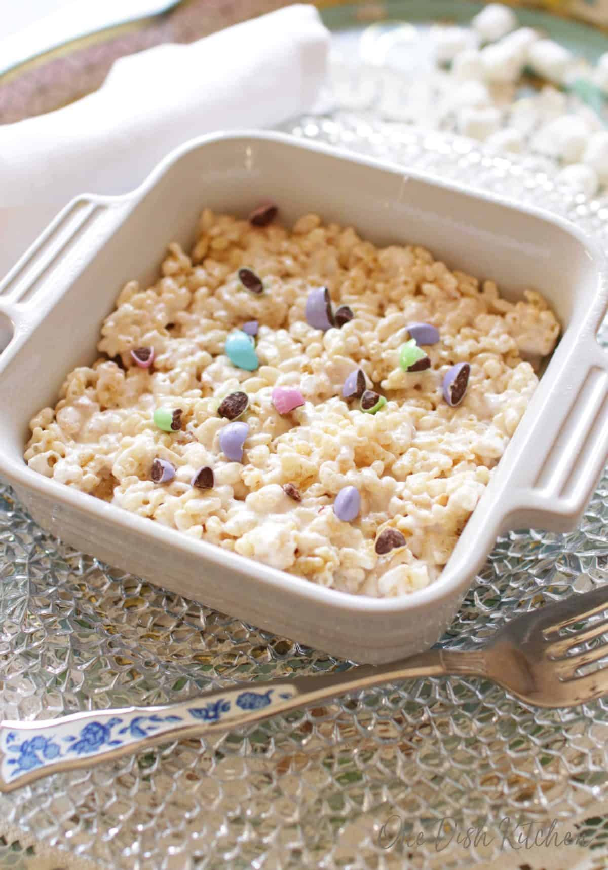 A giant rice krispies treat topped with pastel colored chocolate candies in a small baking dish next to a fork