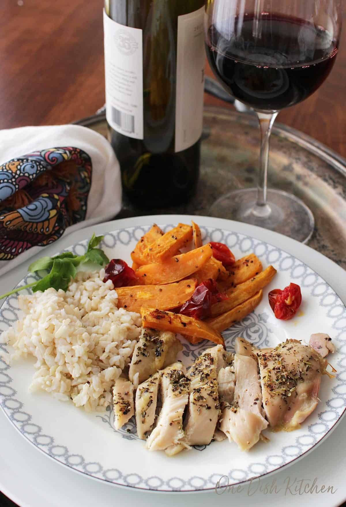 A plate of sliced chicken with roasted sweet potatoes slices, roasted cherry tomatoes, and brown rice next to a glass of red wine all on a metal tray