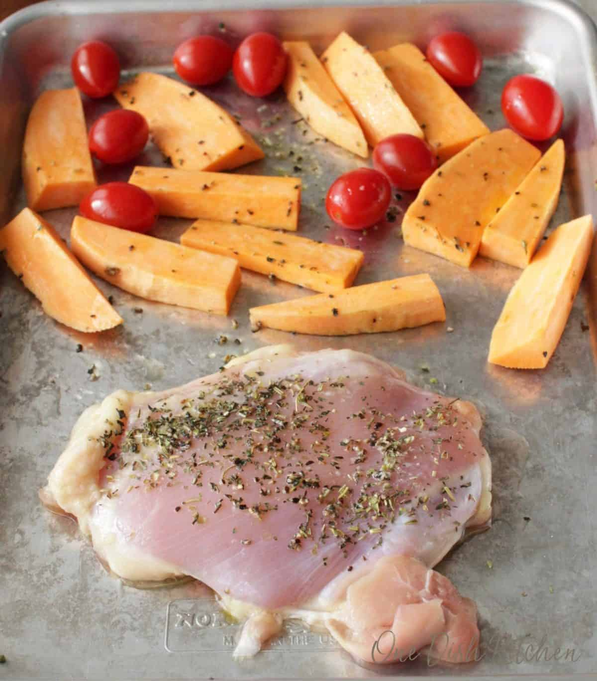 Raw chicken seasoned on a sheet pan along with sweet potato slices and cherry tomatoes
