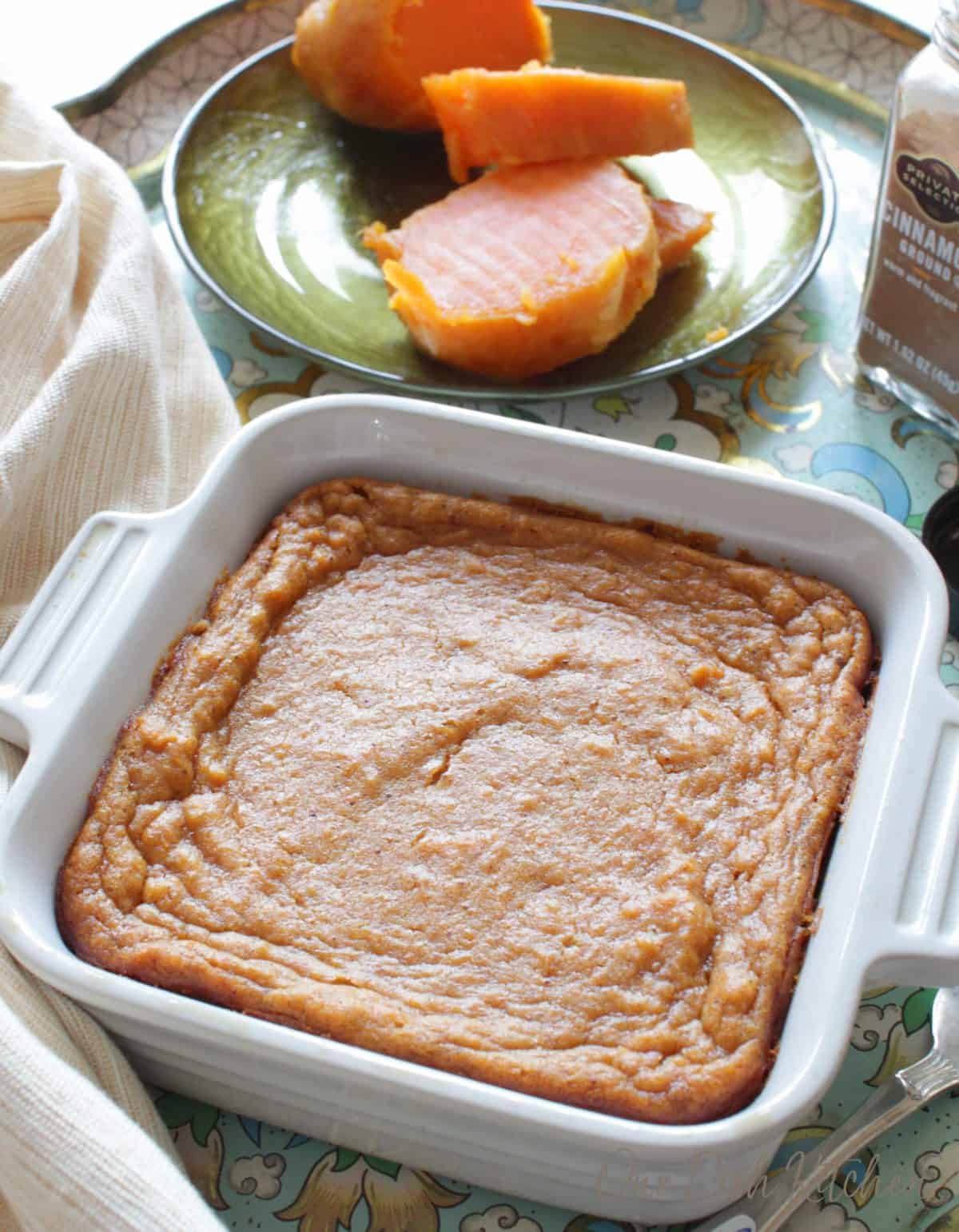 A sweet potato pie in a small baking dish on a tray with a sliced up sweet potato on a plate behind it and a shaker of ground cinnamon