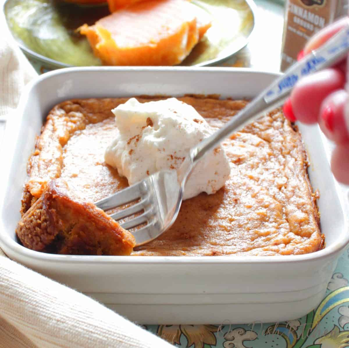 A fork grabbing a piece of sweet potato pie topped with whipped cream