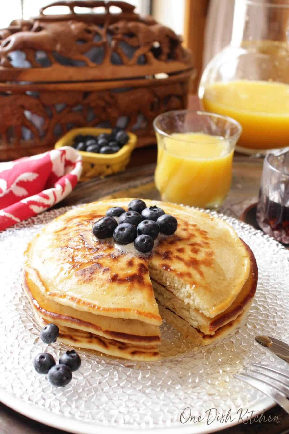 A piece cut out of three pancakes stacked on a plate and topped with melted butter and blueberries next to a small bowl of blueberries, a glass of orange juice, and a small glass container of maple syrup