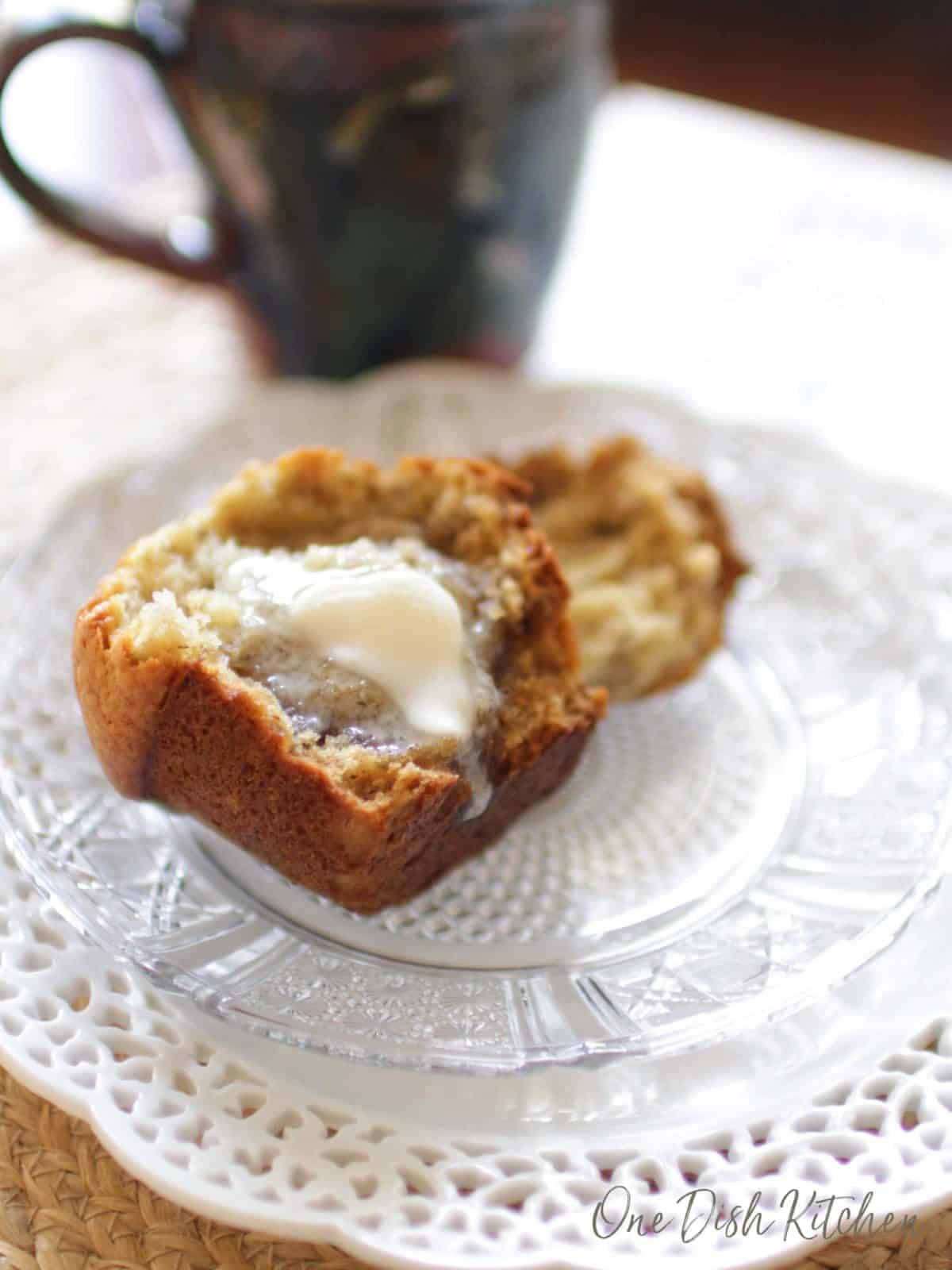Butter melting on a muffin half and dripping onto the plate.