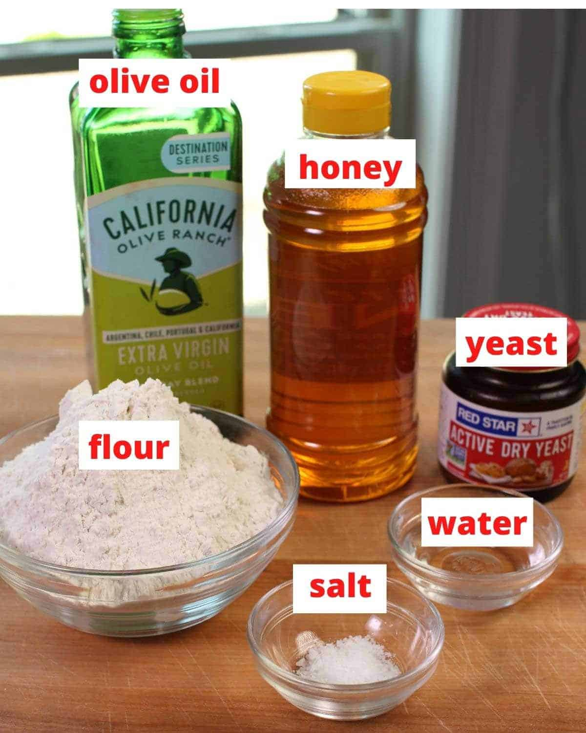 ingredients needed to make french bread including flour, yeast, and water on a wooden table.