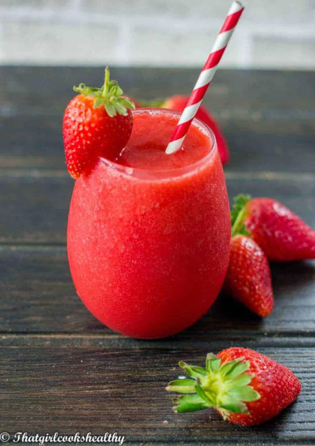 slushie in a glass with strawberries around it
