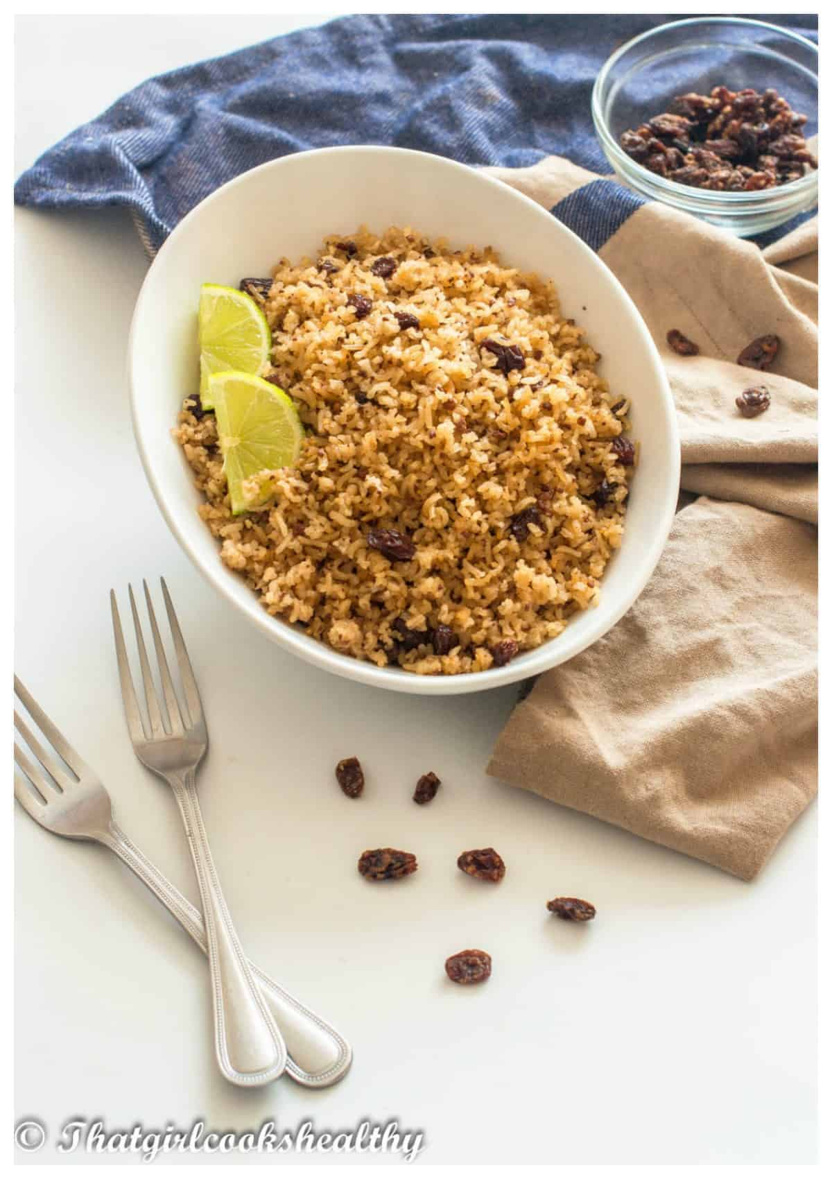 bowl of rice on a cloth with fork and raisins